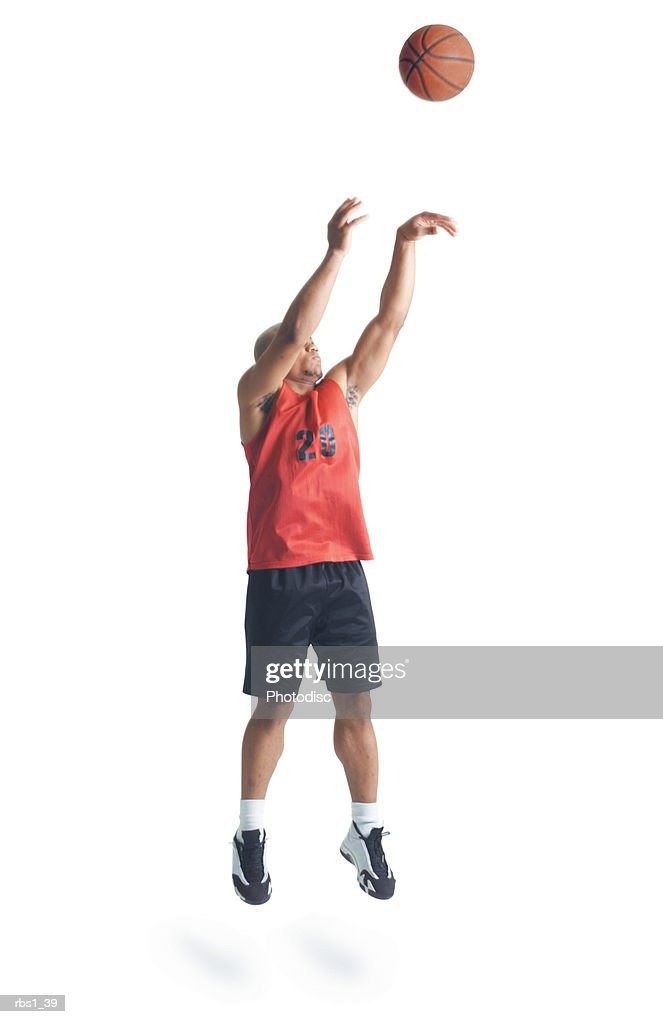 a young african american man is wearing a black and red basketball uniform and jumps high as he shoots the ball : Foto de stock