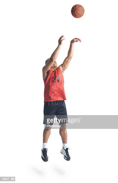 a young african american man is wearing a black and red basketball uniform and jumps high as he shoots the ball - shooting baskets stock pictures, royalty-free photos & images