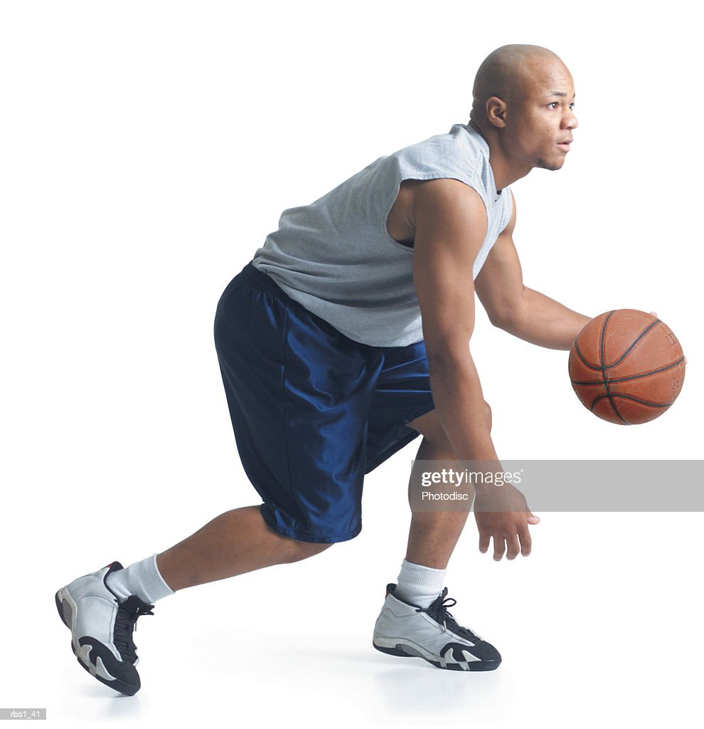 a young african american man wearing blue basketball shorts and a gray tank top is running forward as he dribbles a ball : Foto de stock