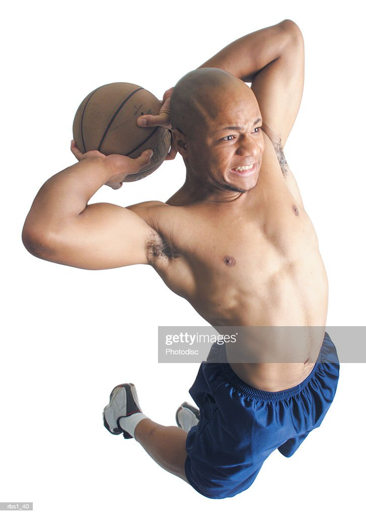 a young african american man wearing blue shorts and no shirt is holding a basketball behind his head and is jumping in the air as he prepares to shoot the ball : Foto de stock