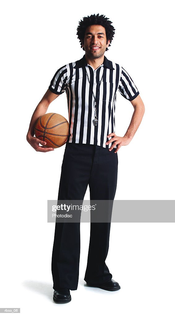 a young african american referee stands with a basketball smiling : Stock Photo