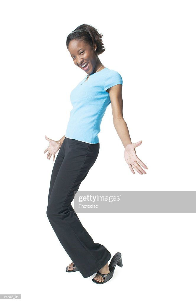 a young african american woman in black pants and a blue shirt spreads out her arms in a fun dance pose : Stockfoto
