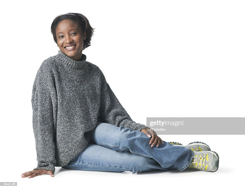 a young african american woman in jeans and a grey shirt sits down on her side and smiles : Foto de stock