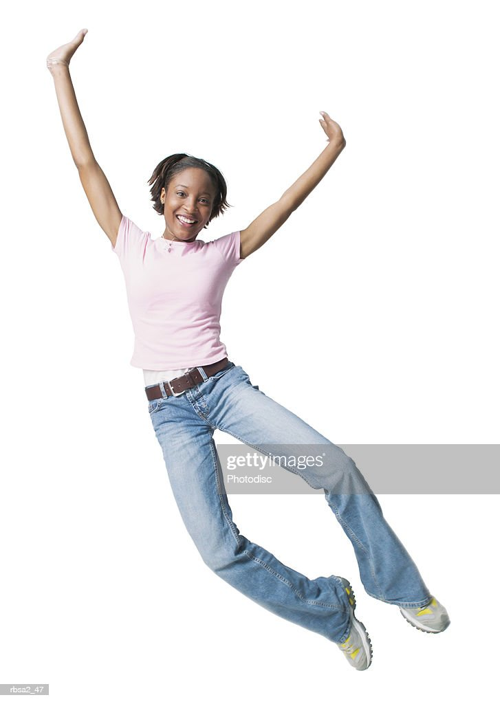 a young african american woman in jeans and a pink shirt jumps up playfully through the air : Foto de stock