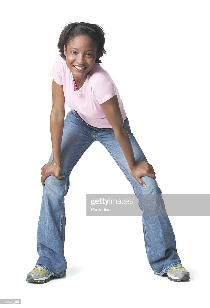 a young african american woman in jeans and a pink shirt leans forward and smiles into the camera : Foto de stock
