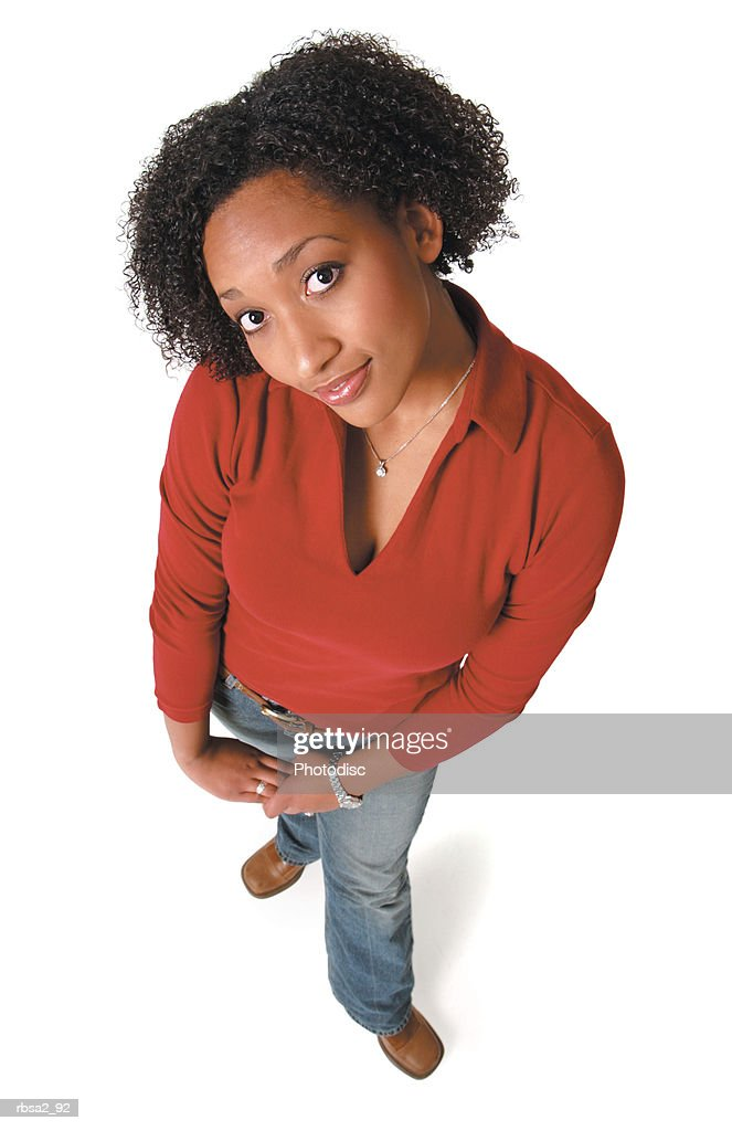 a young african american woman in jeans and a red sweater clasps her hands together and smiles up at the camera : Foto de stock