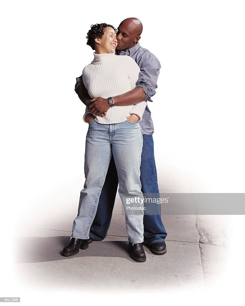 a young african american woman in jeans is standing in front of a young african american man wearing jeans who has his arms around her and is kissing her cheek as she looks back smiling : Foto de stock