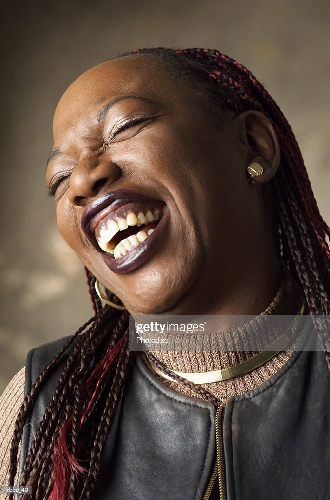 a young african american woman with black and red corn rows is playfully laughing with eyes closed and head thrown back : Stockfoto