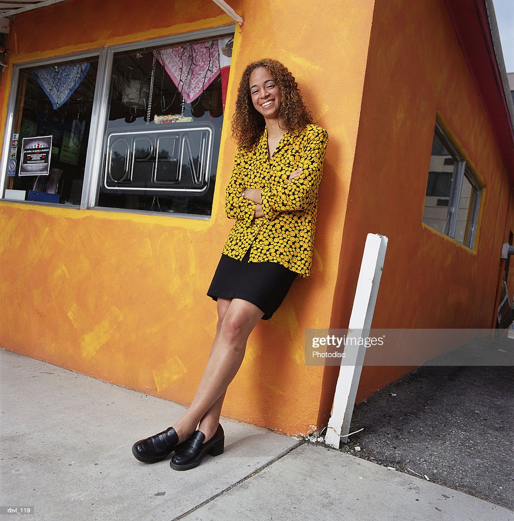 a young african american woman with long brown curly hair in a short black skirt and a yellow polka dot shirt is leaning against an orange building : Foto de stock