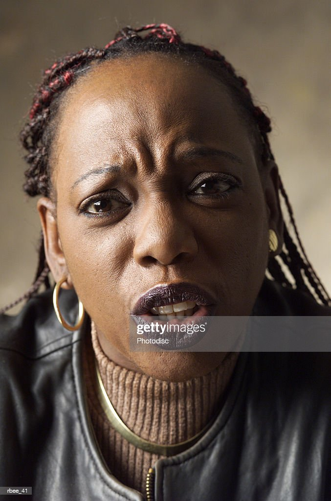 a young African American woman with red and black braids is looking serious with a scolding look : Stockfoto