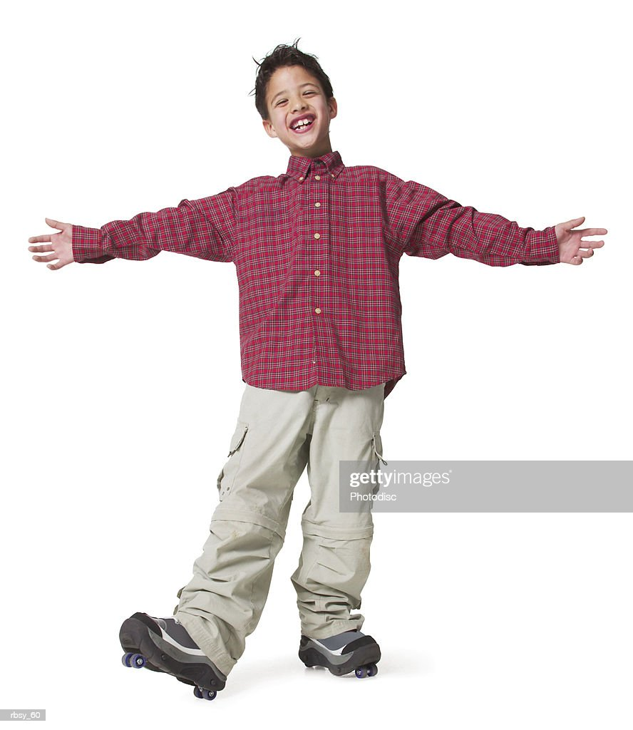a young asian boy in tan pants and a red shirt spreads out his arms as he moves on his roller skates : Foto de stock