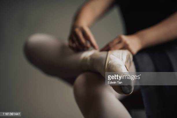 a young asian chinese female ballet dancer getting ready tying her shoelace before practising her ballet dance in ballet studio - preparation stock pictures, royalty-free photos & images