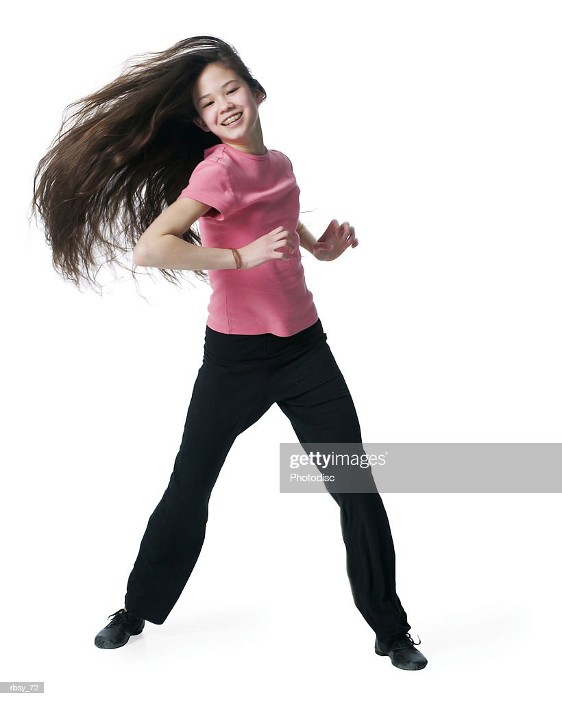 a young asian girl in black pants and a pink shirt dances playfully as she tosses her hair to the side : Foto de stock