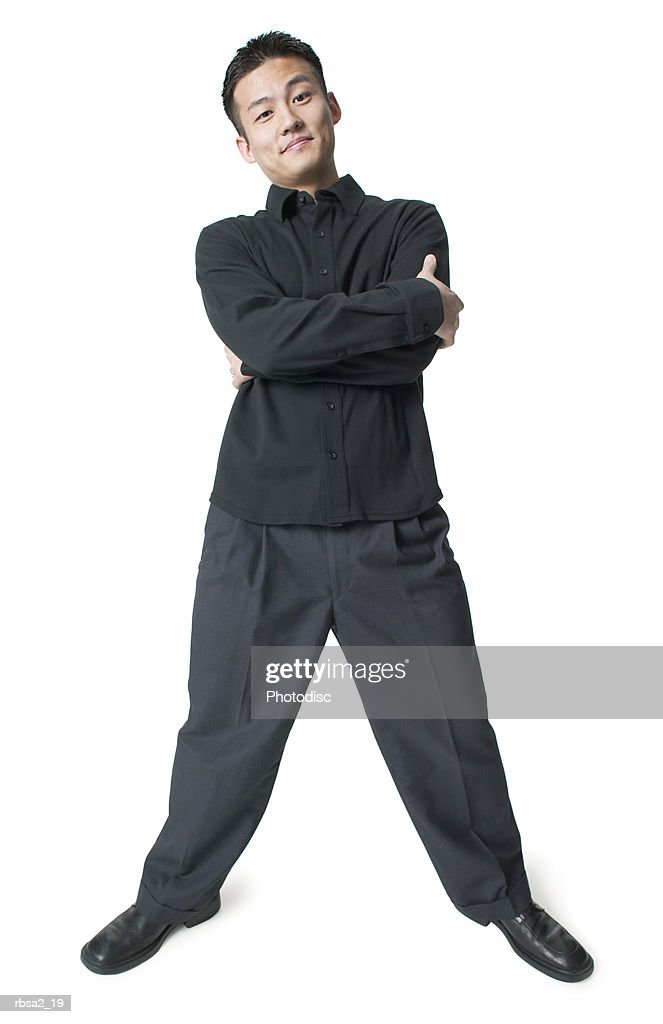 a young asian man dressed in black folds his arms and smiles confidently : Foto de stock