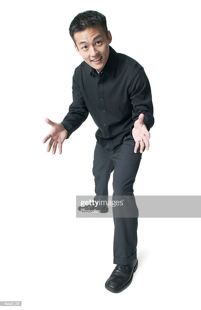 a young asian man dressed in black leans forward and holds out his hands and smiles : Foto de stock