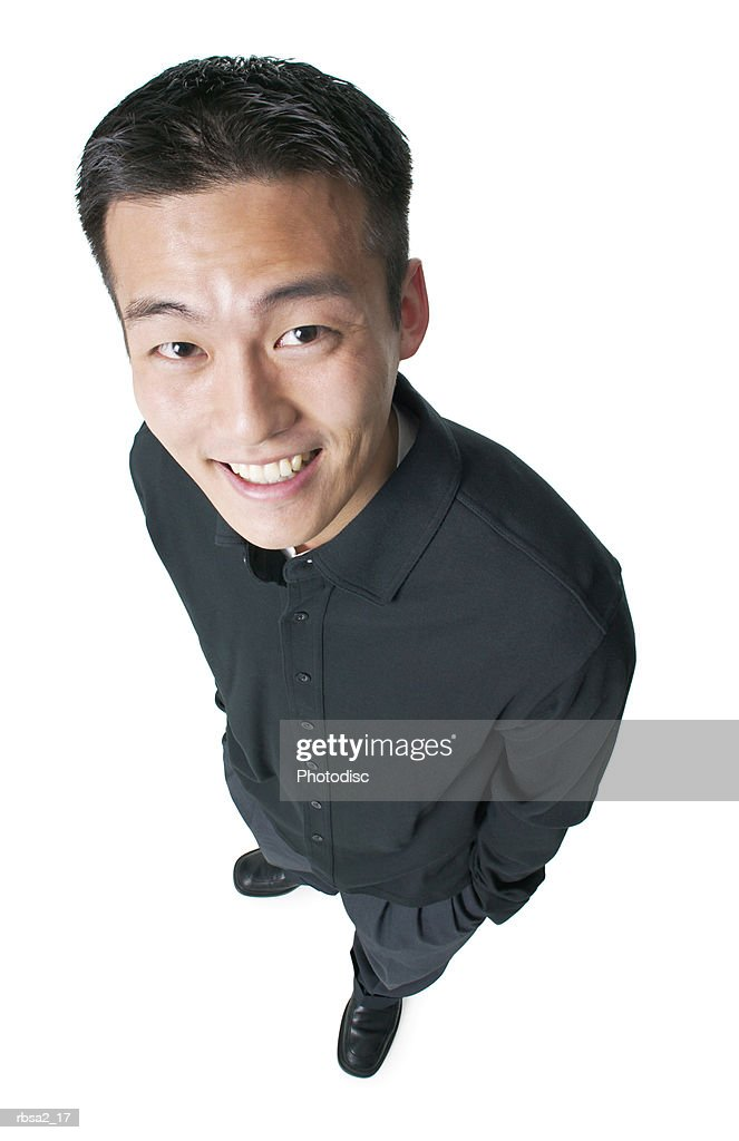 a young asian man dressed in black puts his hands in his pockets and smiles up at the camera : Foto de stock