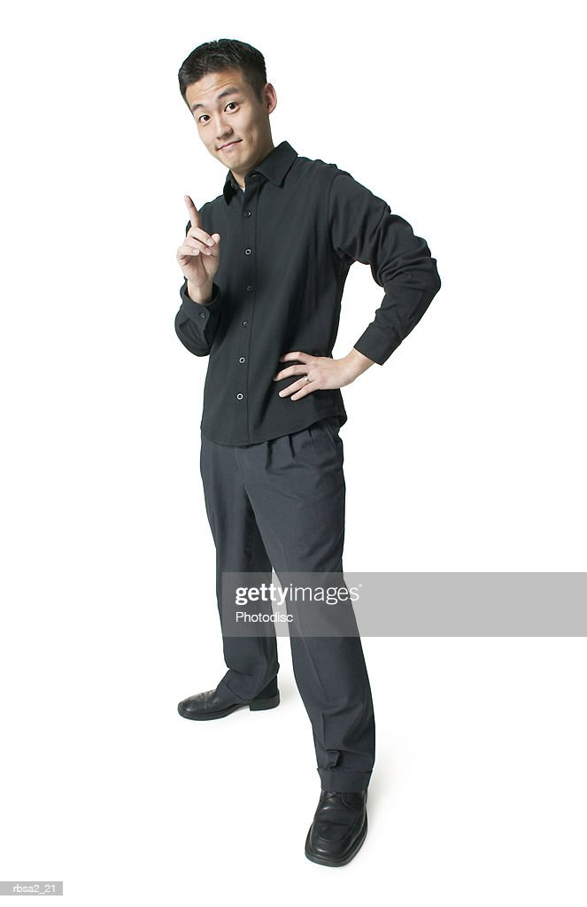 a young asian man dressed in black shakes his finger and smirks at the camera : Foto de stock