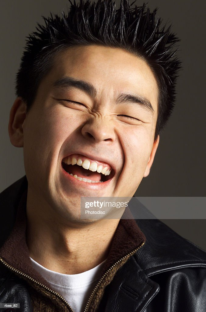 a young asian man with spiked hair and a leather jacket is laughing open mouthed with his eyes shut : Stockfoto