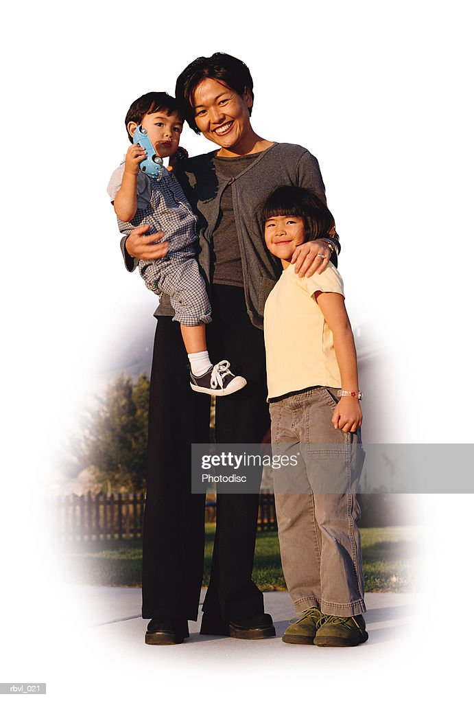 a young asian mother wearing dark pants and blouse is holding her toddler son and has her arm around her little girl as they smile towards the camera : Stockfoto