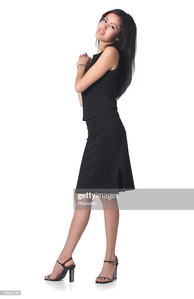 a young asian woman dressed in a black dress clasps her hands together and smiles : Foto de stock
