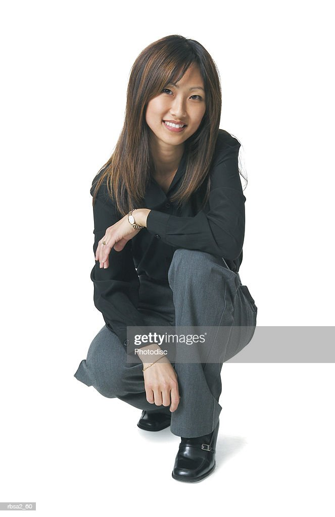 a young asian woman dressed in a black shirt crouches down and smiles at the camera : Foto de stock