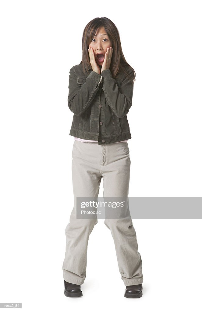 a young asian woman dressed in tan pants and a jean jacket puts her hands on her face and acts shocked and surprised : Foto de stock
