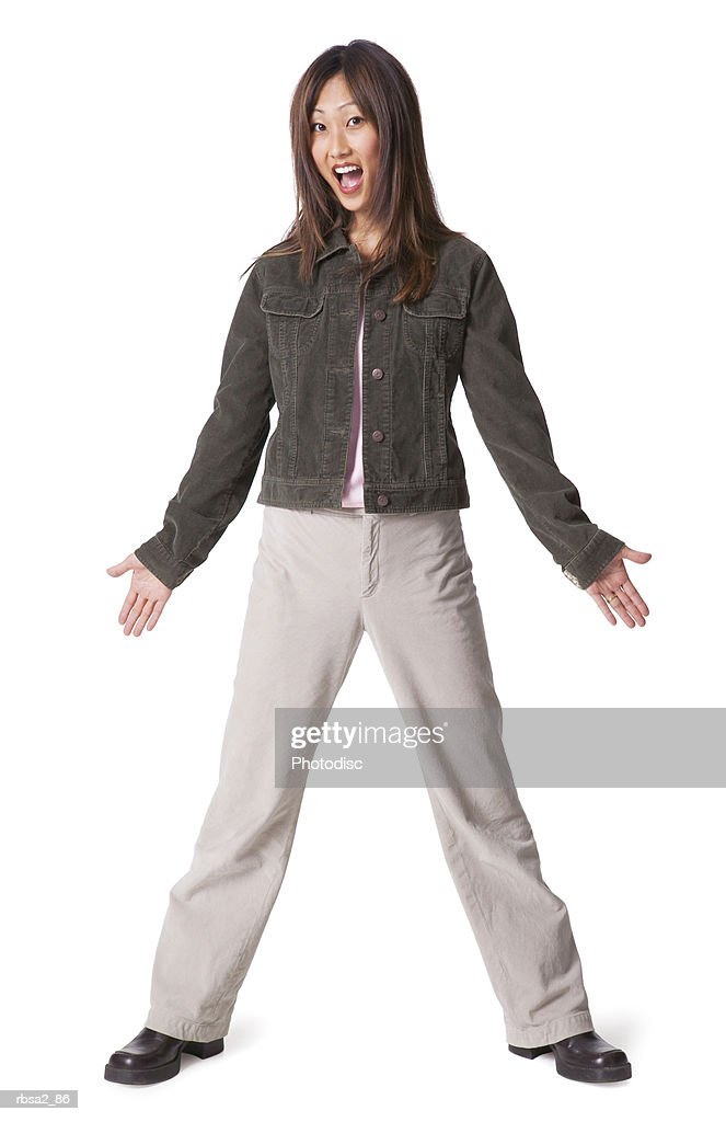a young asian woman dressed in tan pants and a jean jacket spreads out her arms and flashes a surprised expression : Foto de stock