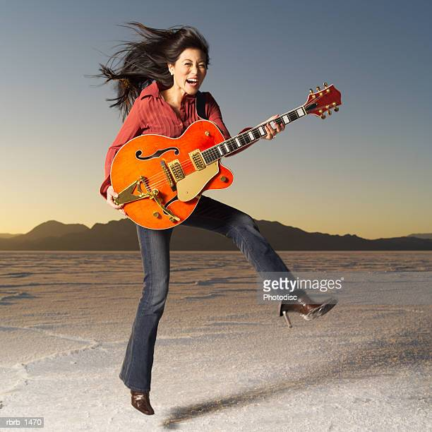 a young asian woman jumps up through the air with a guitar in a desert setting