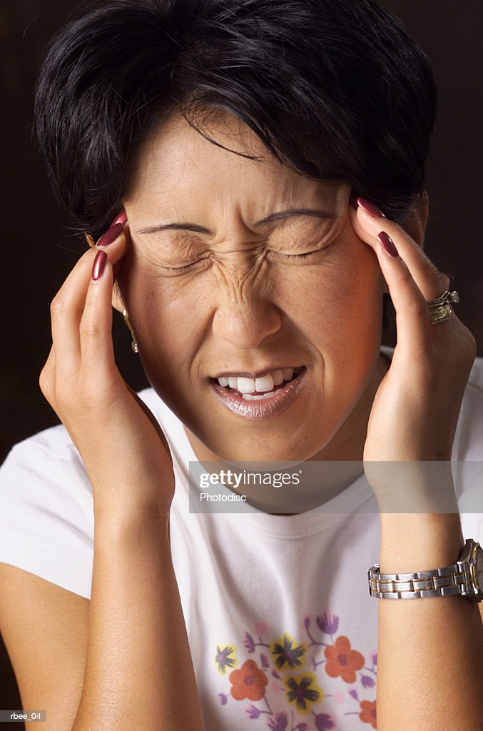 a young asian woman with short hair holds her fingers to her temples and squints her eyes shut as if in pain : Stockfoto