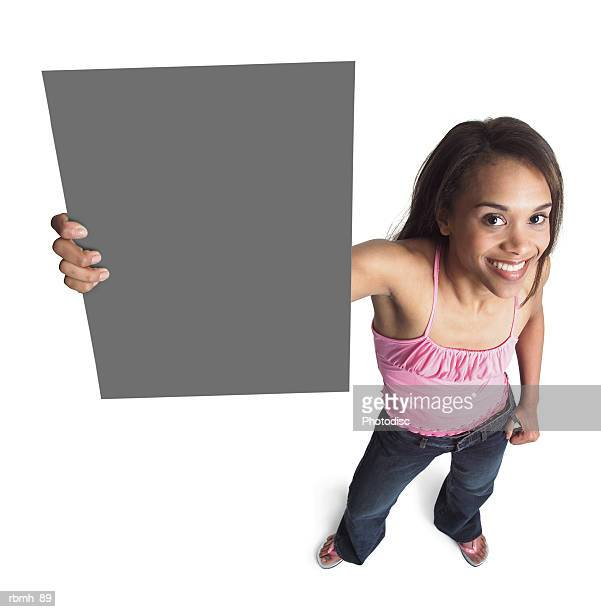 a young attractive african american girl in jeans and a  pink tank top holds a sign up to the side of her head with one arm while she looks up at the camera and smiles - girl wear jeans and flip flops stock photos and pictures