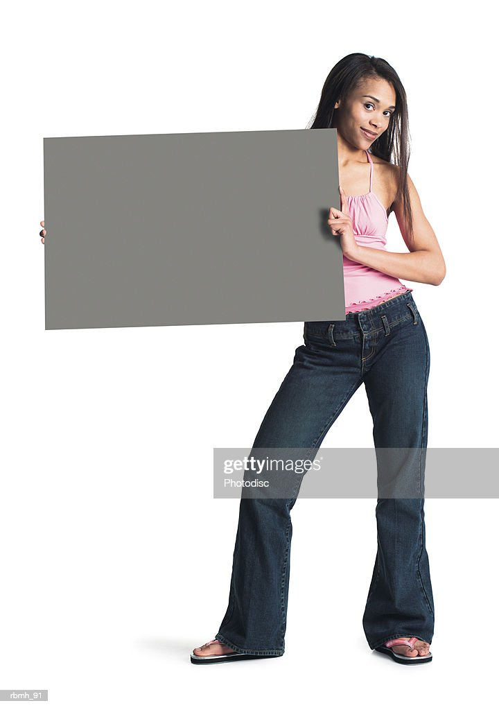 a young attractive african american girl in jeans and a  pink tank top stands with her hips cocked holding a blank sign to one side : Stockfoto