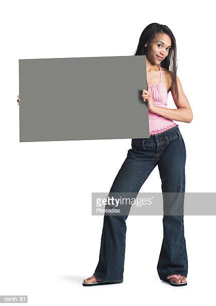 a young attractive african american girl in jeans and a  pink tank top stands with her hips cocked holding a blank sign to one side - girl wear jeans and flip flops stock photos and pictures