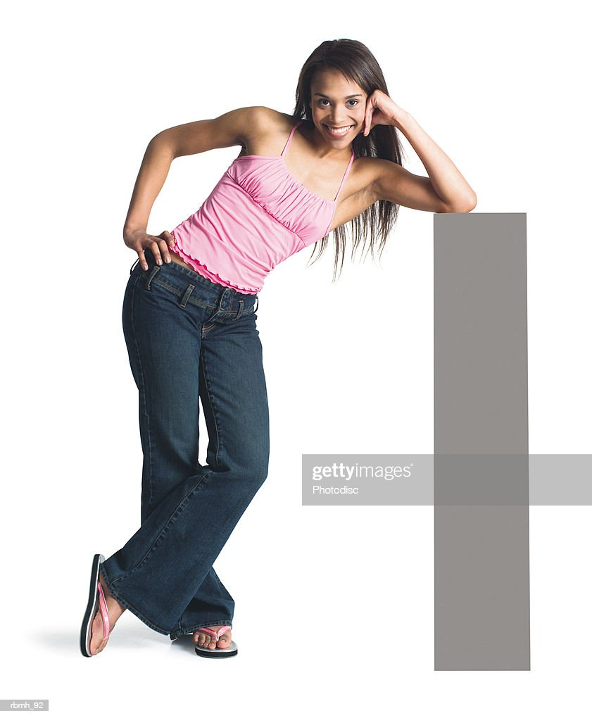a young attractive african american girl in jeans and a  pink tank top stands with her legs crossed and leans on a blank sign propping her head up on her elbow : ストックフォト
