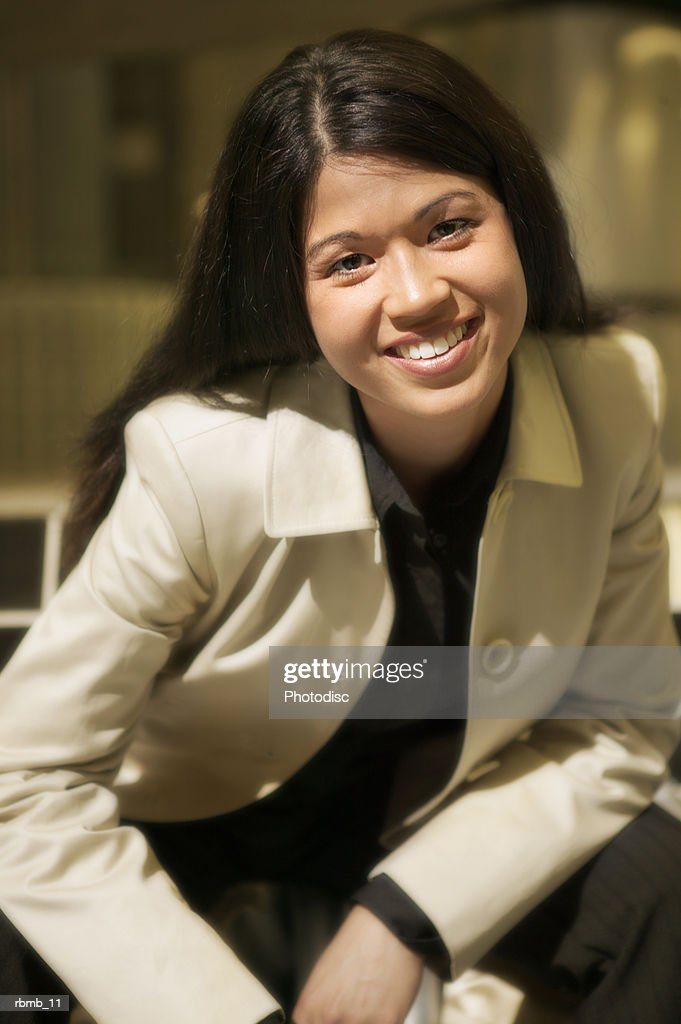 a young attractive asian business woman in a black shirt and tan jacket sits and smiles : Stockfoto