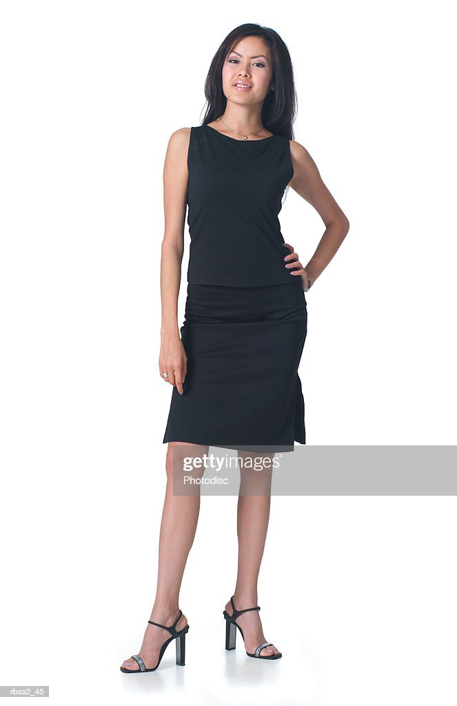 a young attractive asian woman dressed in a black dress puts her hand on her hip and smiles : Foto de stock