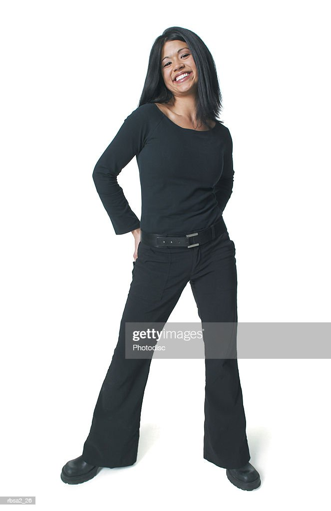 a young attractive asian woman dressed in black puts her hands behind her back and smiles playfully : Foto de stock