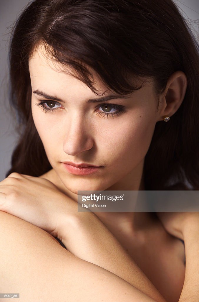 a young attractive caucasian brunette crosses her arms in front of her chest and looks downward : Stockfoto