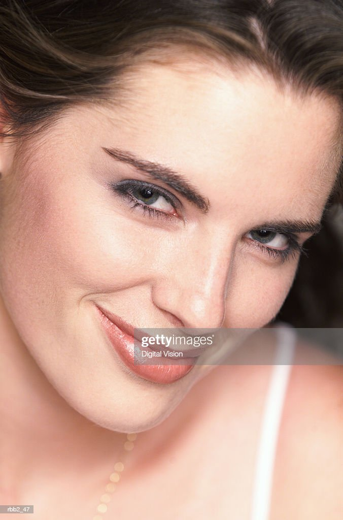 a young attractive caucasian brunette looks up flirtatiously at the camera and smiles : Stockfoto