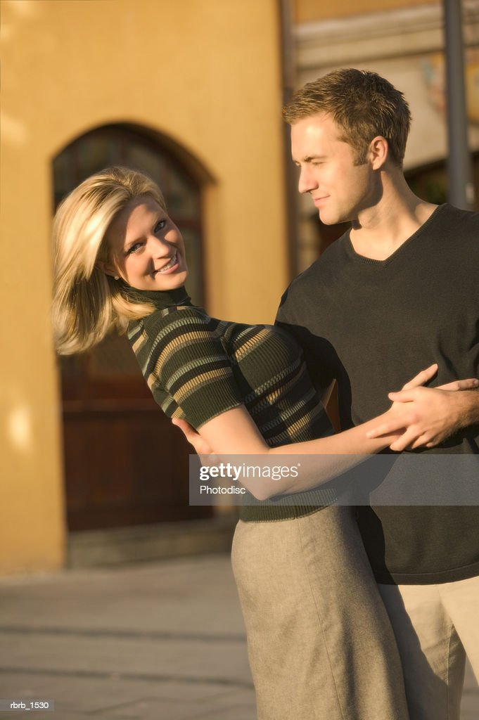 a young attractive caucasian couple playfully embrace while on vacation in europe : Stockfoto