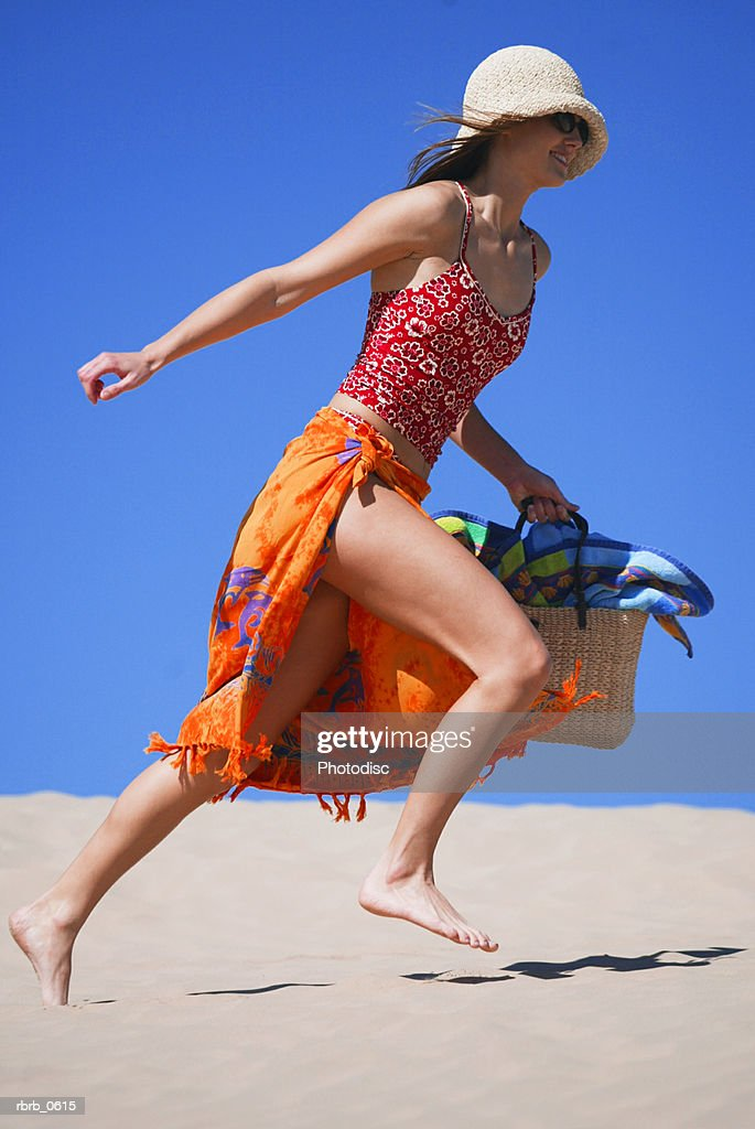 a young attractive caucasian female in a swimsuit hat and sunglasses runs and plays in the sand : Stockfoto