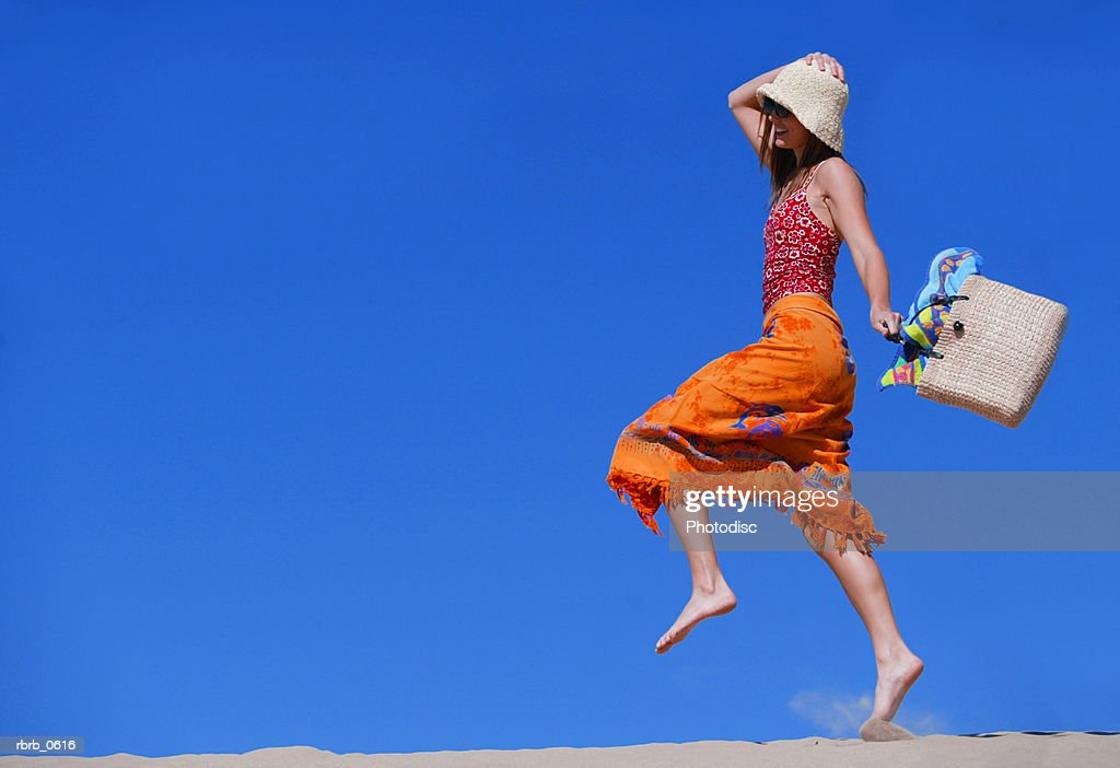 a young attractive caucasian female in a swimsuit hat and sunglasses skips and plays in the sand : Stock Photo