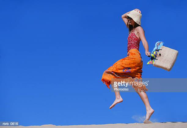 a young attractive caucasian female in a swimsuit hat and sunglasses skips and plays in the sand