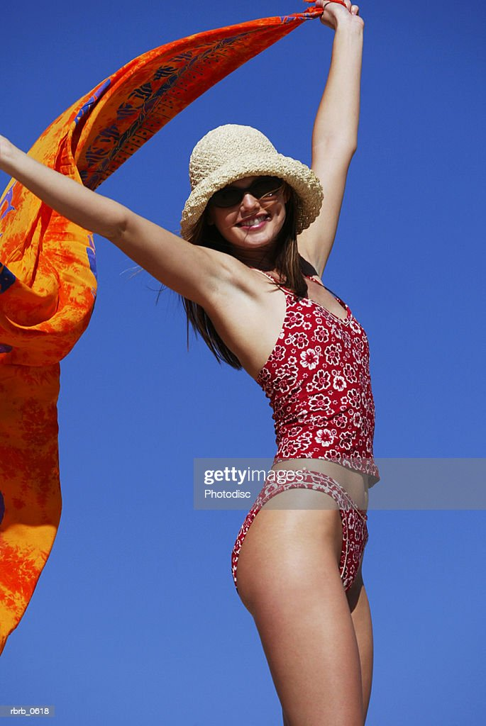 a young attractive caucasian female in a swimsuit hat and sunglasses walks and plays at the beach : Stockfoto