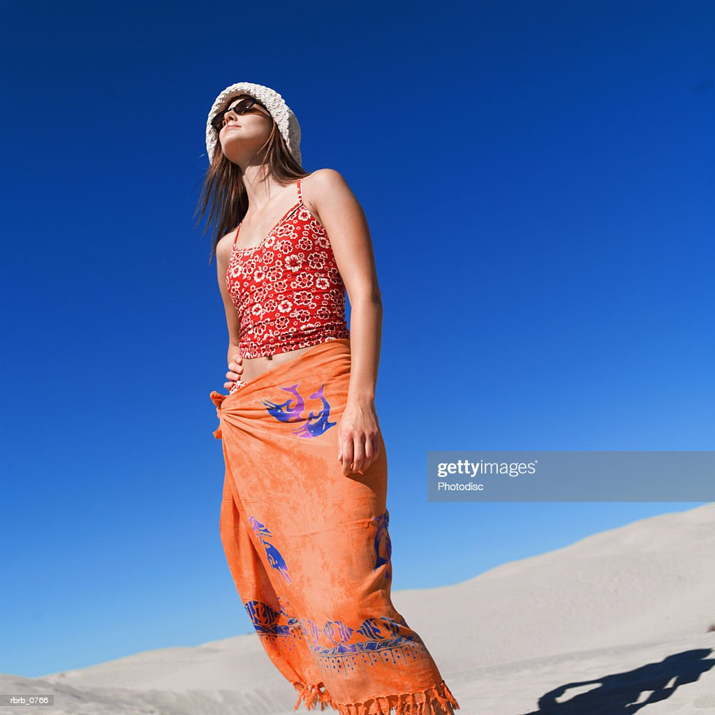 a young attractive caucasian female in a swimsuit hat and sunglasses stands in the sand and looks upward : Stockfoto