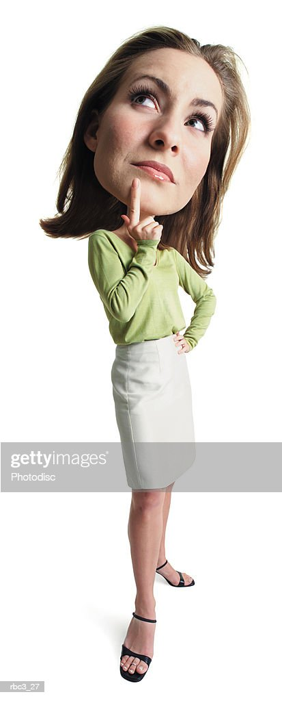 a young attractive caucasian female in a tan skirt and green blouse stands thinking with her finger to her chin : Stock Photo