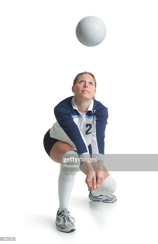 a young attractive caucasian female volleyball player in a blue and white jersey kneels forward preparing to hit a ball flying towards her : Foto de stock