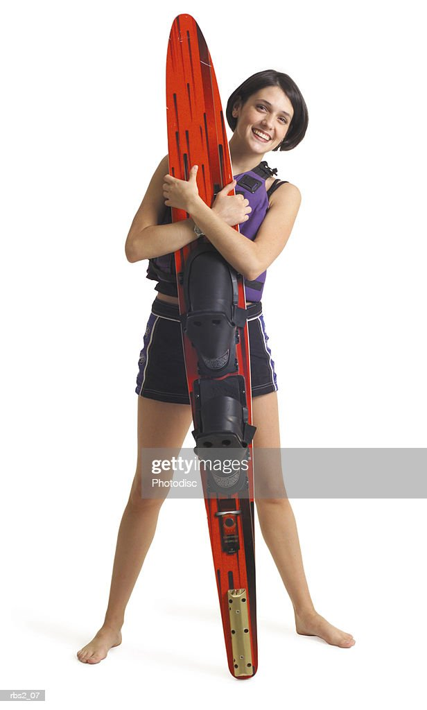 a young attractive caucasian female wearing a life vest and swimming shorts smiles as she stands behind a waterski : Foto de stock