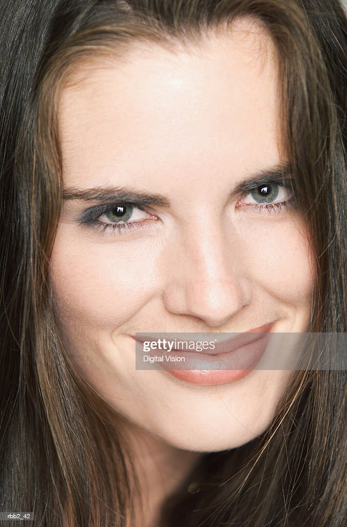 a young attractive caucasian female with brown hair smile smugly while looking into the camera : Stockfoto