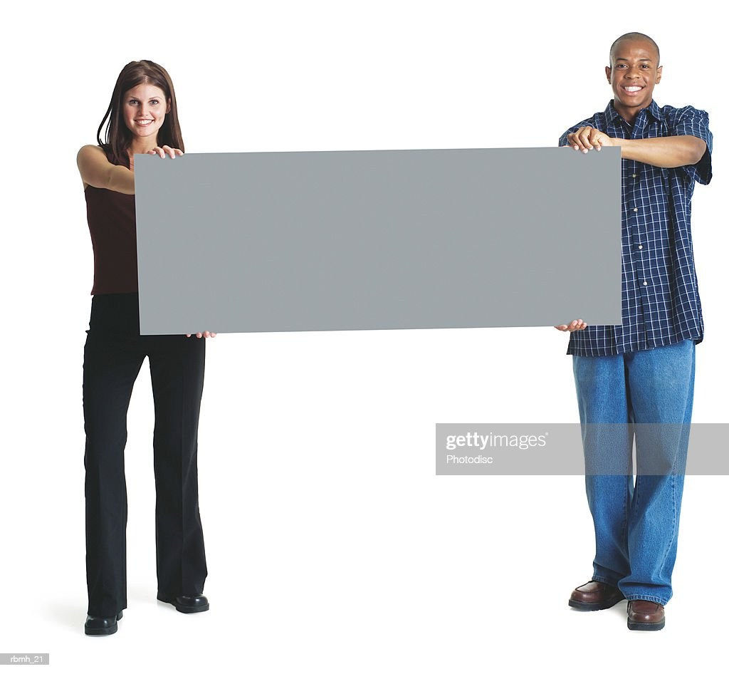 a young attractive caucasian woman and a young african american man hold up a large sign together and smile : Stockfoto