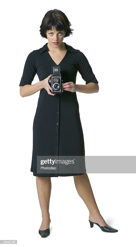 a young attractive caucasian woman in a black dress holds an old camera in front of herself and smiles : Foto de stock